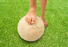 Barefoot kid playing football Stock Image