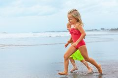 Barefoot kids run along sea beach. Happy barefoot kids have fun on sunset beach walk. Run by water pool along sea surf and jump with splashes. Family travel Royalty Free Stock Image