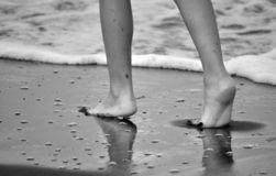 Barefoot legs on the beach. stock photo