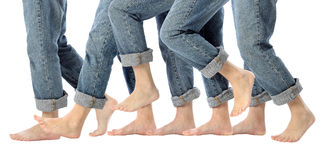 Barefoot Legs in Motion. A womans bare feet advance one step forward in rolled up jeans on white stock photo