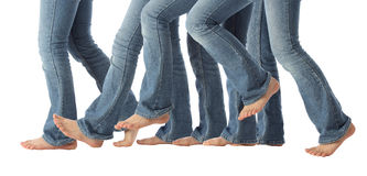 Barefoot Legs in Motion. A young girls bare feet advance one step forward in jeans on white stock photo