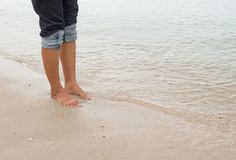 Barefoot legs walking in the seashore, Vacation on summer sea Royalty Free Stock Photography
