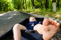 Barefoot little boy inside a suitcase Stock Image