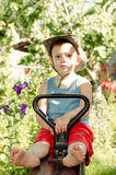 Barefoot little boy playing in the garden. In a trendy hat as he sits on a rustic seesaw staring at the camera Stock Images