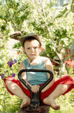 Barefoot little boy playing in the garden. In a trendy hat as he sits on a rustic seesaw staring at the camera Royalty Free Stock Images