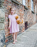 Barefoot Little Girl next to Brick Wall Royalty Free Stock Images