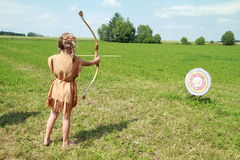 Barefoot little girl shoting with bow to a target Stock Photos