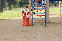 Barefoot little girl in skirt goes on sand Royalty Free Stock Photography