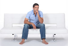 Barefoot man. Sitting on a modern couch and wondering Royalty Free Stock Images