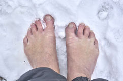 Barefoot man. Man standing barefoot in fresh snow stock photos