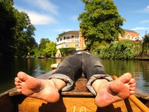 Barefoot man on boat Oxford England punting. Barefoot man reveals the souls of his bare feet as he sunbathes on a punting boat in a river in Oxford, England Stock Images