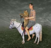 Man and his cat on the pony 3 stock images