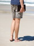 Barefoot man holding agenda book at the beach Stock Photos