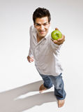 Barefoot man holding fresh green apple Stock Photo