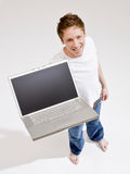 Barefoot man holding laptop Stock Photography