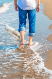Barefoot man in jeans walking on the sea Stock Photos