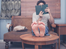 Barefoot man reading at home Stock Image