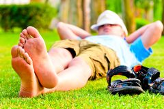 Barefoot man is resting on green grass Royalty Free Stock Photos