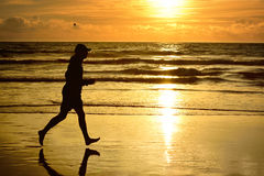 Barefoot man running ocean beach sunset. Royalty Free Stock Image