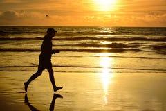 Barefoot man running ocean beach sunset. Royalty Free Stock Image