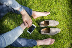Barefoot man sitting on grass Royalty Free Stock Photos