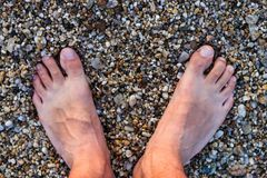 Barefoot Man Standing On The Rocky Beach.  Royalty Free Stock Photos