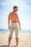 Barefoot man stands on sandy summer beach Royalty Free Stock Image