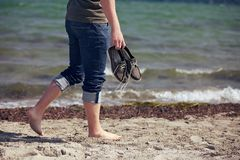 Barefoot Man Walking Along the Sandy Beach Royalty Free Stock Image