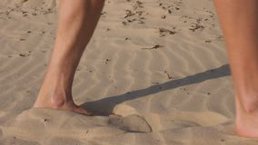 Barefoot man walking on desert sand closeup. Male shadow and footprint on sand. Barefoot man walking on sandy dunes in desert close up. Male legs walking on sand stock video
