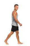 Barefoot Man Walking. Young man in black shorts and gray shirt walking barefoot and looking at camera. Side view. Full length studio shot isolated on white Royalty Free Stock Photos