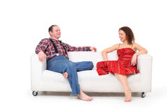 Barefoot man and woman sit on white leather sofa Royalty Free Stock Photo