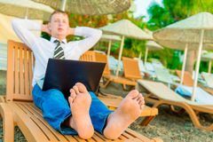Barefoot manager on a sun lounger Stock Images