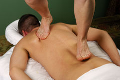 Barefoot Massage. Young man receiving a barefoot massage by masseuse at day spa salon Royalty Free Stock Photo