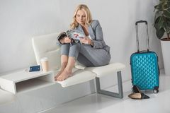 Businesswoman with magazine waiting for trip. Barefoot mature businesswoman reading magazine while waiting for trip Royalty Free Stock Photos
