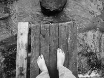 Barefoot on an old wooden bridge stock images
