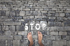Barefoot person and stop sign message Royalty Free Stock Images