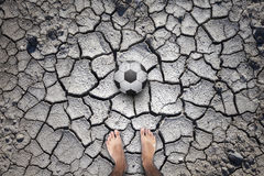 Barefoot player with soccer ball. Soccer ball on soil drought cracked football field with barefoot player legs. Personal perspective used stock photo