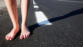 Barefoot and road. Barefoot girl on the road Royalty Free Stock Images