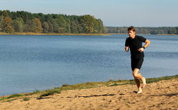 Barefoot runner running on a beach Royalty Free Stock Images