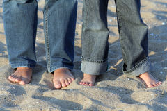 Barefoot in the sand. Two pairs of jeans dressed legs barefoot on a sandy beach Royalty Free Stock Photo