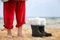 Barefoot Santa Claus and boots. On beach Royalty Free Stock Photography