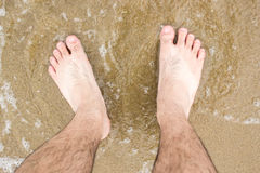 Barefoot in sea with foam Stock Images