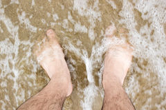 Barefoot in sea with foam Royalty Free Stock Images
