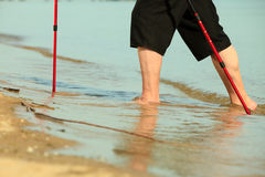 Barefoot senior nordic walking on a beach. Stock Photography