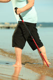 Barefoot senior nordic walking on a beach. Royalty Free Stock Photography