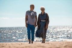 Chill at resort. Barefoot seniors walking down sandy beach during summer chill on sunny day at resort stock photo