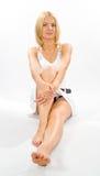 Barefoot sitting girl. Beautiful girl sitting on floor,barefoot on white background royalty free stock image