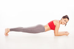 Smiling young woman practicing push-up exercises Stock Images