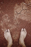 Barefoot standing on dry cracked Stock Image