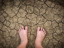Barefoot standing on dry and cracked ground Stock Photography